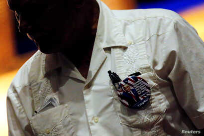 FILE - A man wears a Trump campaign button on his traditional guayabera shirt at a Hispanic Town Hall meeting with U.S. Republican presidential nominee Donald Trump and supporters in Miami, Fla., Sept. 27, 2016.