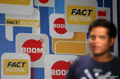 A crew member walks in front of a hoarding displaying the logo of BOOM, one of Facebook Inc's fact-checking partners in India, at a studio in Mumbai, India, March 12, 2019.