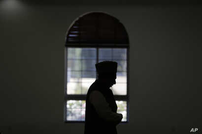 FILE - An imam prays at a mosque in Chino, California, Nov. 18, 2016. Targeting clerics opposed to the Islamic State in a new propaganda campaign, the jihadist group is thought to have launched an effort aimed at deligitimizing them, especially in th...