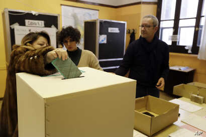 A voter casts her ballot in Rome, Sunday, March 4, 2018.