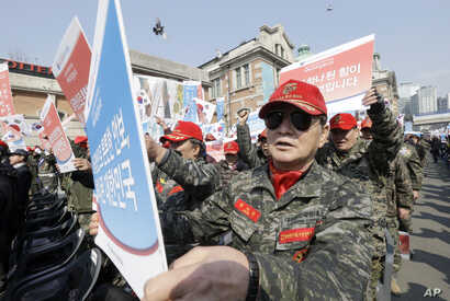 South Korean war veterans hold up their placards during a rally denouncing North Korea's recent threat in Seoul, South Korea, March 25, 2016.