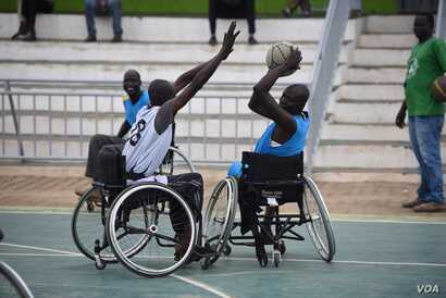 A wheelchair basketball player tries to block a pass by an opponent at a basketball court in Juba, South Sudan, May 24, 2016.