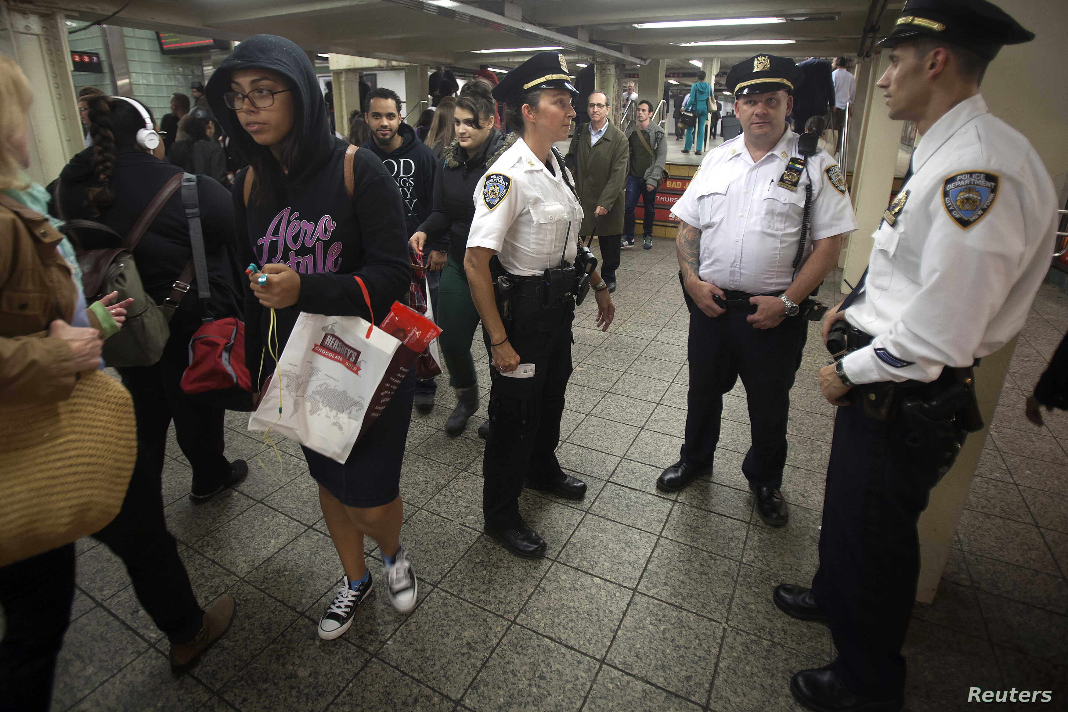 Members of the New York Police Department stand and talk at the Times Square subway station in the Manhattan borough of New York, Sept. 25, 2014.