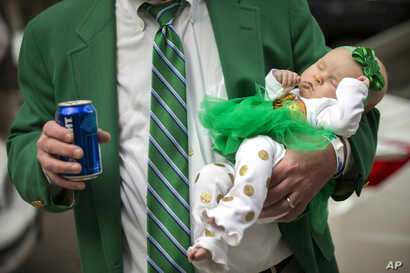 Joey Homans holds his 3-month-old granddaughter Caroline Homans in one hand and a beer in the other before the start of the Savannah St. Patrick's Day parade, March 16, 2019, in Savannah, Ga.