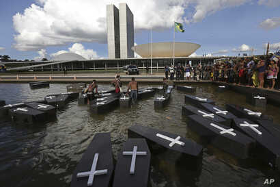 Indigenous protesters from various ethnic groups place fake coffins, representing Indians killed over the demarcation of land, in a reflecting pool outside the National Congress as they demand the demarcation of indigenous lands in Brasilia, Brazil, ...