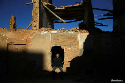 Tomas Ortin, 94, survivor of the Belchite battle, sits in the ruins of his former home in Belchite, in northern Spain, Nov. 14, 2016.