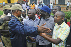 Uganda's main opposition leader Kizza Besigye (2nd R, blue cap) and his supporters are blocked by policemen during a Walk to Work protest in the Kasangati suburb near Uganda's capital Kampala, Uganda, October 18, 2011.