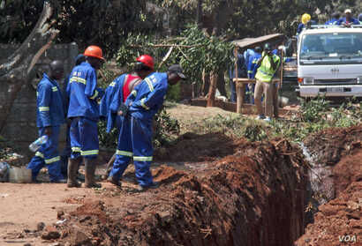 Workers trying to unblock a sewer pipe in Harare, Zimbabwe, Sept. 11, 2018, which residents say has been like that for at least three months.