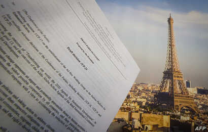 An illustration picture taken on Dec. 10, 2015 in Paris shows a draft for the outcome of the COP21 United Nations conference on climate change next to a picture of the Eiffel Tower.