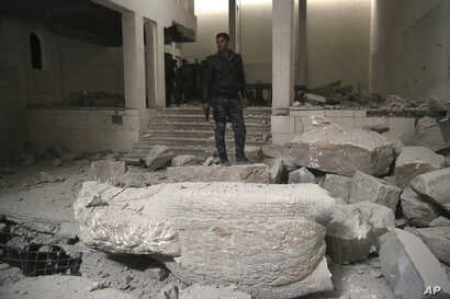 Iraqi federal police inspect the inside of Mosul's heavily damaged museum, March 8, 2017. Two Iraqi archaeologists confirmed that many of the artifacts destroyed by IS were the original ancient stone statues dating back thousands of years.