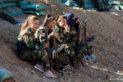 Iranian-Kurdish female fighters hold their weapons during a battle with Islamic State militants in Bashiqa, near Mosul, Iraq Nov.  3, 2016.