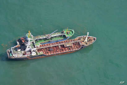 FILE - This May 24, 2018, photo released by Japan's Ministry of Defense shows the North Korean-flagged tanker Sam Jong 2, bottom, alongside the Myong Ryu 1, a vessel of unknown nationality, in the East China Sea. Japan's Foreign Ministry says a Japan...