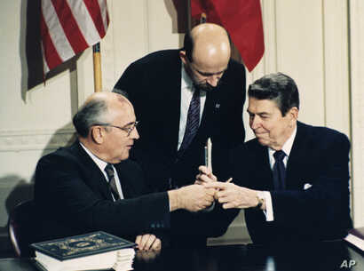 FILE -  U.S. President Ronald Reagan (R) and Soviet leader Mikhail Gorbachev exchange pens during the Intermediate Range Nuclear Forces Treaty signing ceremony in the White House East Room in Washington, D.C., Dec. 8, 1987.