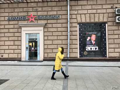 A woman walks by a Russian Army store displaying a poster of Donald Trump across from the U.S. embassy in Moscow, Jan. 20, 2016. (D. Schearf/VOA)