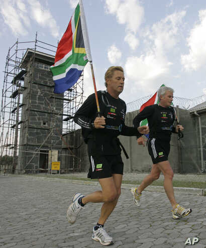 South African runner Braam Malherbe, left, and Dawid Grier run past the prison where former South African President Nelson Mandela spent most of the 27 years that he was jailed, during his 90th birthday celebration on Robben Island, South Africa, Jul...