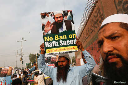 A supporter of Islamic charity organization Jamaat-ud-Dawa (JuD) carries a sign during a protest demonstration...