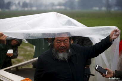 Chinese dissident artist Ai Weiwei speaks to reporters as he holds a rain cover to protect Syrian musician Nour Alkhzam from the rain, after her performance in a field near a makeshift camp on the Greek-Macedonian border, near the village of Idomeni,...