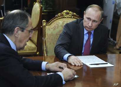 Russian President Vladimir Putin, right, listens to Russian Foreign Minister Sergey Lavrov during their meeting in the Kremlin in Moscow, Russia, March 14, 2016.