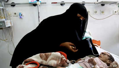 In this Tuesday, March 22, 2016 photo, Udai Faisal, who is suffering acute malnutrition is fed by his mother Intissar Hezzam at al-Sabeen Hospital in Sanaa, Yemen.