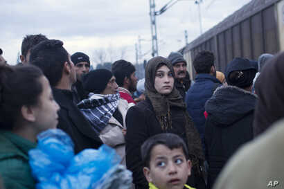 A woman stands in a crowd beside the railway tracks as a train passes beside a refugee camp where thousands of refugees are waiting to be allowed to cross the border into Macedonia in the northern Greek border station of Idomeni, Thursday, March 3, 2...