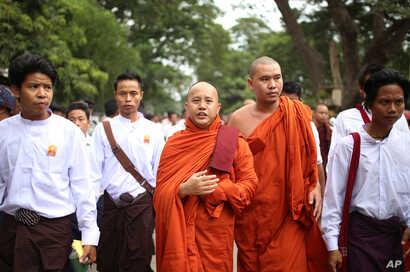 Nationalist Buddhist monk Wirathu, center, marches to celebrate newly imposed restrictions on interfaith marriages in Mandalay, the second largest city in Myanmar, Sept. 21, 2015.