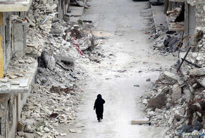 A woman walks past damaged buildings in the rebel-controlled area of Maaret al-Numan town in Idlib province, Syria, May 13, 2016.