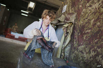FILE - Forensic scientist Cristina Cattaneo collects post-mortem data from a shipwreck victim at the NATO base in the Sicilian town of Melilli, Italy, Oct. 8, 2016.
