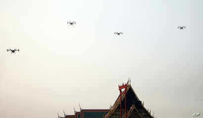 Water-spraying drones fly over the Suthat Temple in Bangkok, Thailand, Thursday, Jan. 31, 2019. A fleet of drones, trucks and small planes are spraying water to try to reduce dust around Bangkok while the governor invited critics to brainstorm better...