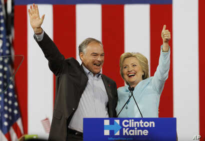 Democratic U.S. vice presidential candidate Senator Tim Kaine (D-VA) waves with his presidential running-mate Hillary Clinton after she introduced him during a campaign rally in Miami, Florida, U.S. July 23, 2016.