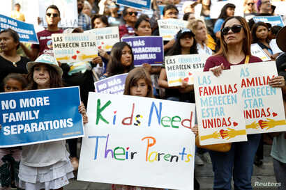 People hold signs to protest against U.S. President Donald Trump's executive order to detain children crossing the southern U.S. border and separating families outside of City Hall in Los Angeles, California, June 7, 2018.