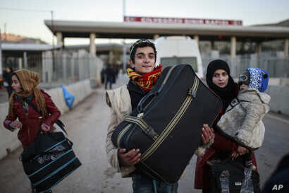 Members of a Syrian family carry their belongings after they crossed into Turkey at the Cilvegozu border gate with Syria, near Hatay, southeastern Turkey, Dec, 18, 2016.