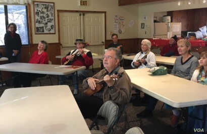 Steve Winget (center) and other seniors at the San Jose Ukulele Club's 2016 Christmas Jam follow the lyrics on a screen at the front of the room.