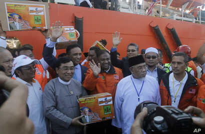 Myanmar Social Welfare Minister Win Myat Aye, second from left, receives aid from Malaysian officials after a Malaysian ship full of aid for the Muslim Rohingya minority arrived at Thilawa port in Yangon, Myanmar, Feb. 9, 2017.