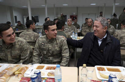 FILE - Hulusi Akar, Turkey's defense minister and former chief of staff, speaks with soldiers during a visit to Turkish troops stationed at the border with Syria, in Kilis, Turkey, Dec. 31, 2018. Russian and Turkish foreign and defense ministers met ...