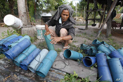 FILE - Cambodian farmer Suon Yom, 45, clears tubes before loading them with palm juice at Prey Pong-Ro village near Phnom Penh, Cambodia, Jan. 2, 2015.