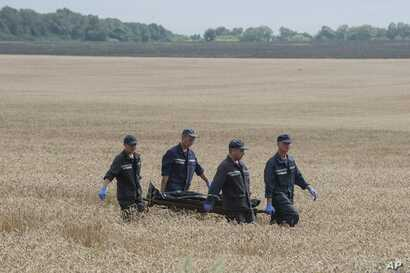 Emergency workers carry a stretcher with a victim's body in a bag at the crash site of a Malaysia Airlines jet near the village of Hrabove, eastern Ukraine,  July 19, 2014.