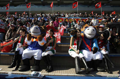 FILE - Mascots and attendants from the Hong Kong Jockey Club sit on the spectators' stand at Shatin race track in Hong Kong, Dec. 11, 2011. A large share of losing bets contributes directly to the welfare of Hong Kong's society through charitable con...