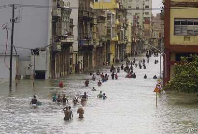 APTPeople move through flooded streets in Havana after the passage of Hurricane Irma, in Cuba, Sept. 10, 2017.