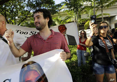 """FILE - Thomas Kennedy, 25, protests outside of a rally for Republican presidential nominee Donald Trump, in Miami, Sept. 16, 2016. """"One of the things that scares me the most is that this wretched man, Trump, wins,"""" said Kennedy. After becoming a natu..."""