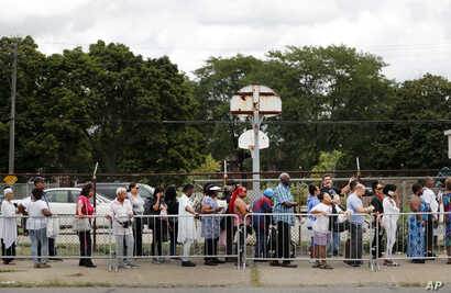 People stand in a line stretching for blocks outside New Bethel Baptist Church to pay their respects to legendary singer Aretha Franklin, Aug. 30, 2018, in Detroit. Franklin died Aug. 16, 2018.