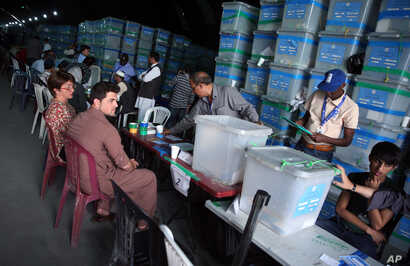 FILE - Afghan election commission workers sort ballots for an audit in front of international observers at an election commission office in Kabul, Afghanistan, Aug. 27, 2014.