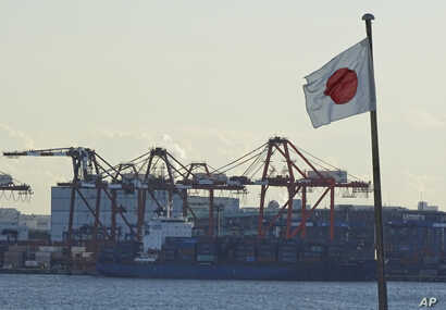 FILE - A Japanese flag is hoisted near the pier of a container terminal in Tokyo, Jan. 25, 2017.