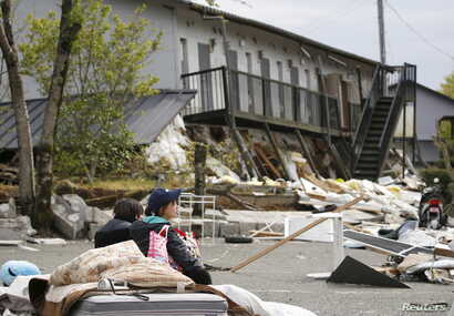 A university student takes a rest in front of an apartment building ravaged by earthquakes in Minamiaso town, Kumamoto prefecture, southern Japan, in this photo taken by Kyodo, April 16, 2016.