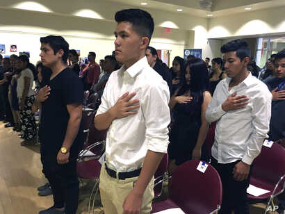 FILE - Long Chi Vong, 16 (C), from Albuquerque, and other immigrants stand for the U.S. Pledge of Allegiance before taking the Oath of Citizenship at a ceremony in Rio Rancho, N.M., Aug. 19, 2016
