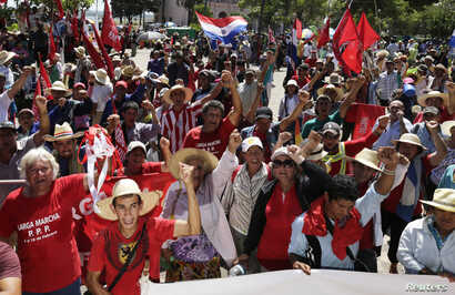 FILE - Paraguayan peasants march during a protest in the streets of downtown Asuncion, Feb. 10, 2015. The protesters marched to the front of the Congress building and presented their demands on land reform and other issues.