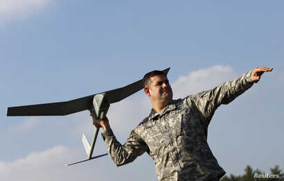U.S. soldier Randell Atkinson poses in the starting position with a Raven drone during its official presentation by the German and U.S. Unmanned Aerial Systems at the U.S. military base in Vilseck-Grafenwoehr, Germany, Oct. 8, 2013.