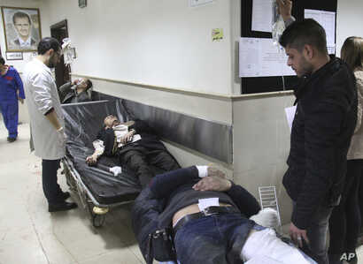 In this photo released by the Syrian official news agency SANA, Syrian injured men wait to receive medical treatments after they wounded in the main judicial building, which was attacked by a suicide bomber, in Damascus, Syria, March 15, 2017.