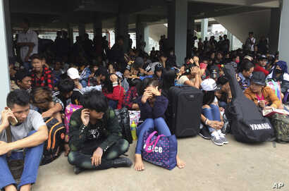 FILE - Myanmar workers wait before leaving Thailand at Mae Sot Immigration office in Tak province Thailand, July 3, 2017.