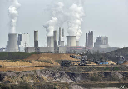Machines dig for brown coal in front of a smoking power plant near the city of Grevenbroich in Germany. The Paris Agreement, which formally starts November 4, 2016, in the Pacific region, seeks to wean the world economy off fossil fuels in the second...
