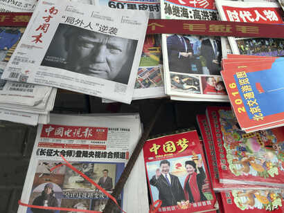 """FILE - front page of a Chinese newspaper with a photo of U.S. President-elect Donald Trump and the headline """"Outsider counter attack"""" is displayed at a newsstand in Beijing, China."""